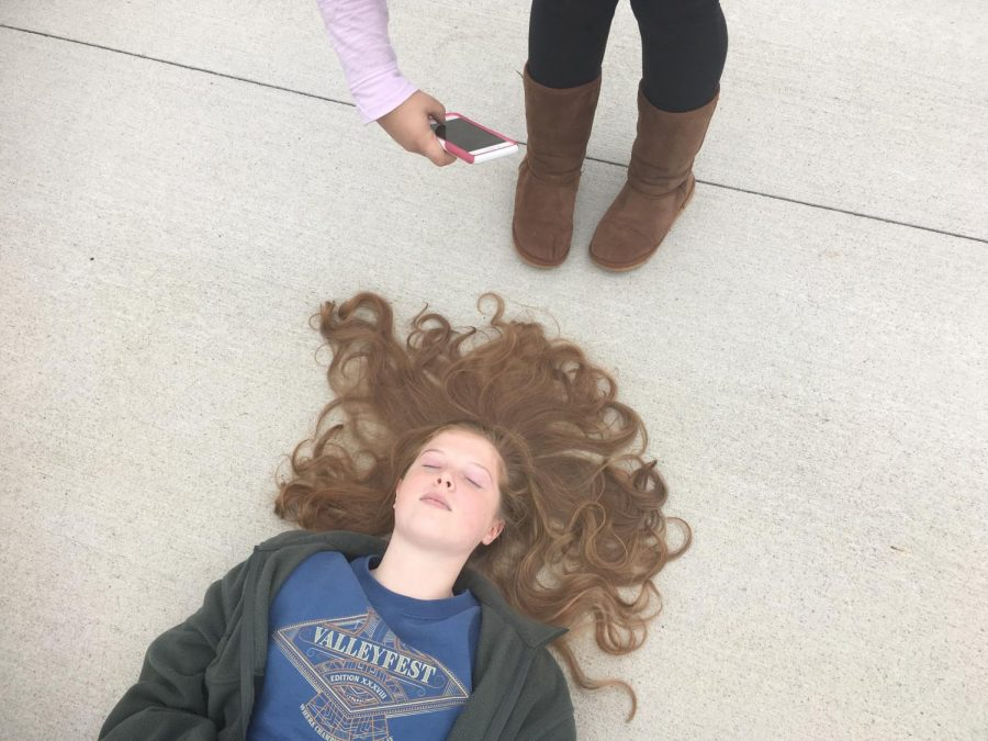 Katrina Feinberg '19 lies down for a photo op taken by Jailyn Alderman '19. Digital Photo works outside as part of the landscape assignment.