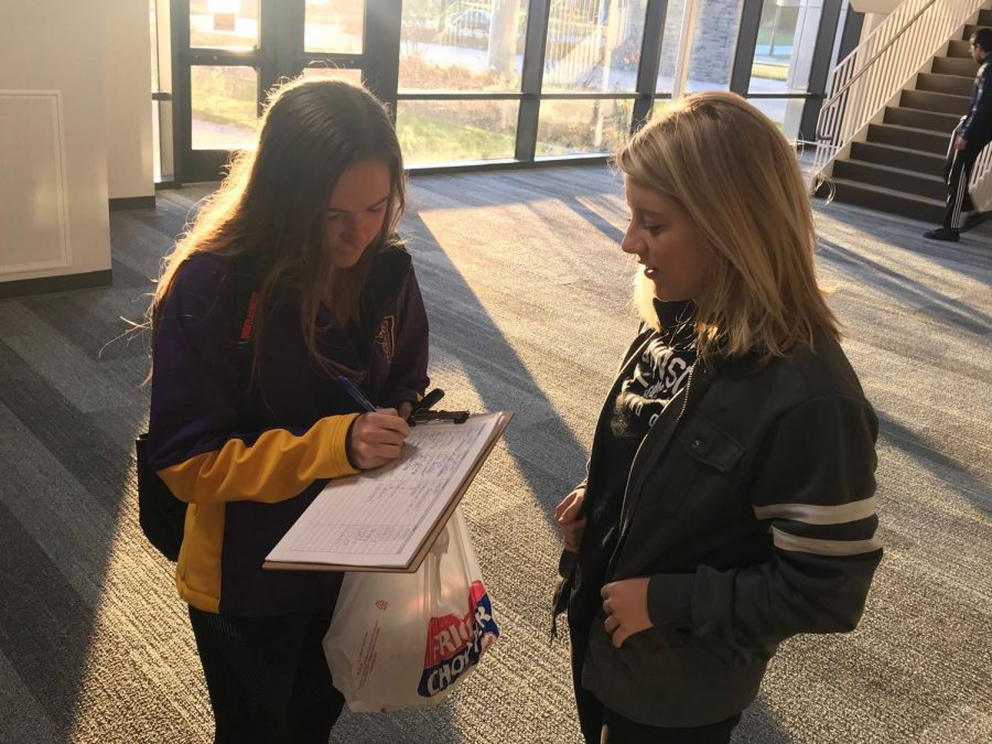 Josie Barsness '18 watches as Anika Schmitt '18 signs the petition she created for the handprint wall.