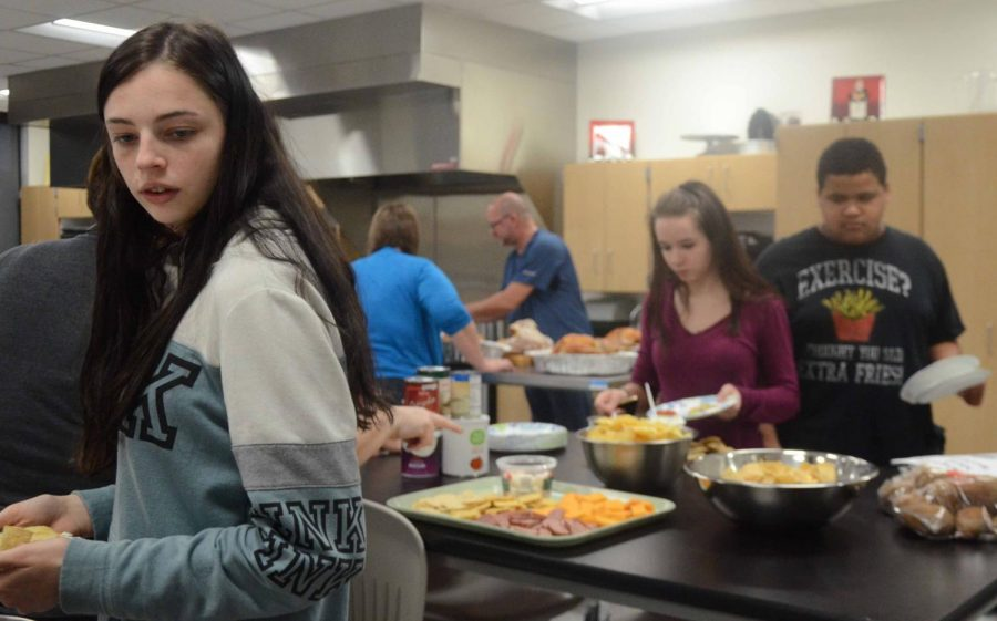Madison Heston 19 grabs a snack before cooking. Most of the foods were cracker sandwiches and chips that kids could eat between cooking dishes.