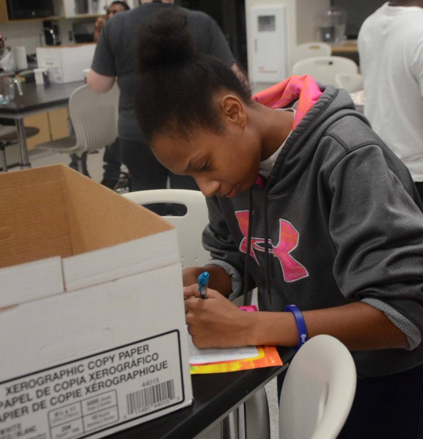 Karma Johnson 20 iwrites a letter of thanks to HyVee for donating food for the activity. Each participant signed the card to HyVee with short messages.