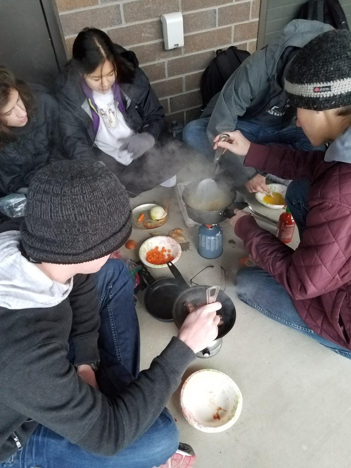 Track six students cook pasta with different supplies they brought.