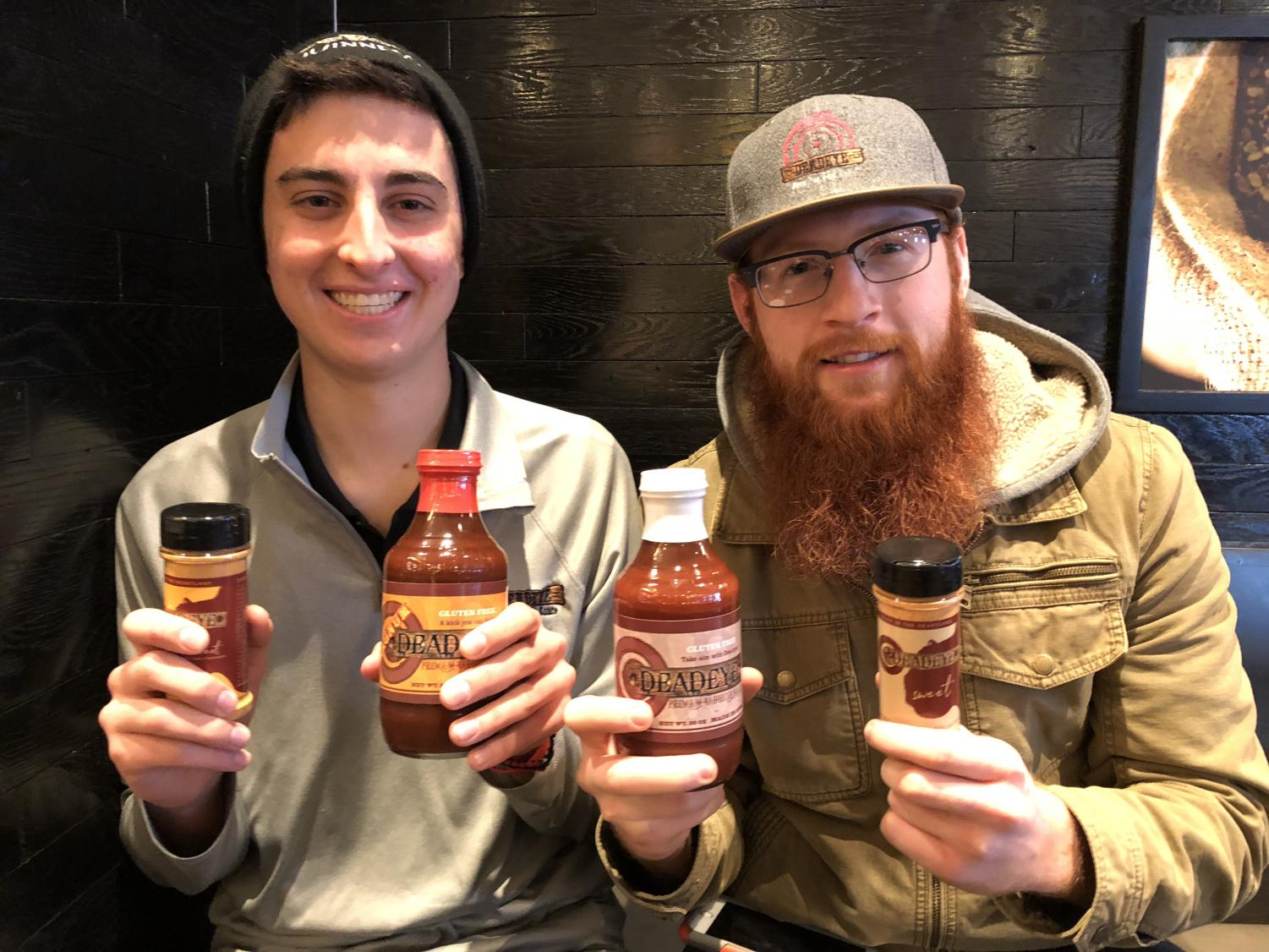 Hanstad and Devos show the Deadeye BBQ sauce. The business was founded by the two when they were freshmen.