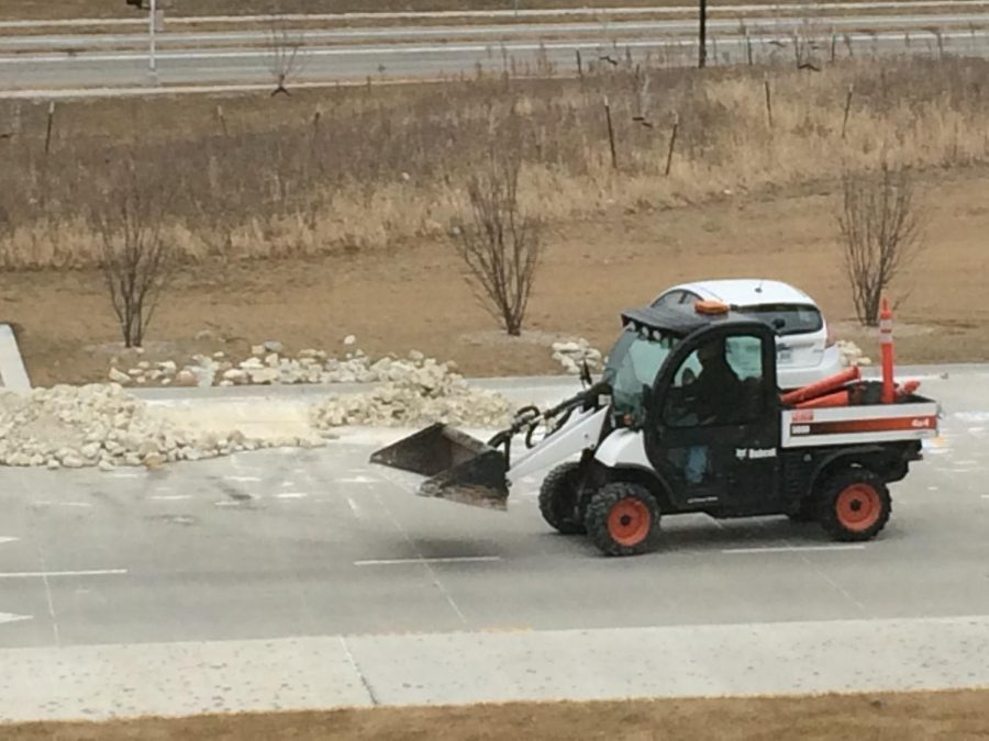 Bobcat loader transports the landscaping rocks from the student parking spots.