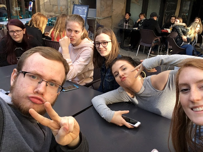 """Alisa Capehart, Christian Schiller, JD Norris, and Sloane Wilhelm are seated with Alisa's and JD's host students. """"[All of us] got together and we went on a walk and we stopped at this restaurant and got something to drink,"""" Capehart said."""