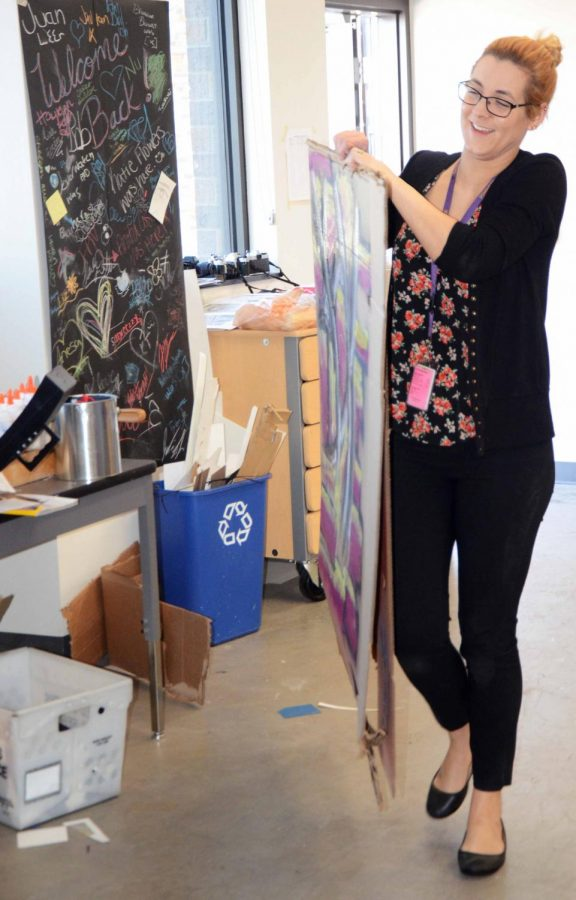 Art teacher Katie Black carries multiple pieces inside after everyone has finished painting. Black dabbled in spray paint when she was younger, though recently has not messed with it.
