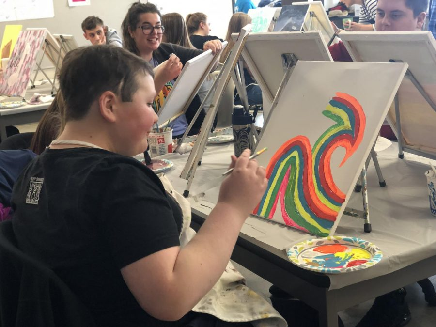 Jack Marren paints layers of different colored waves. The Best Buddies painting party was held on January 20.