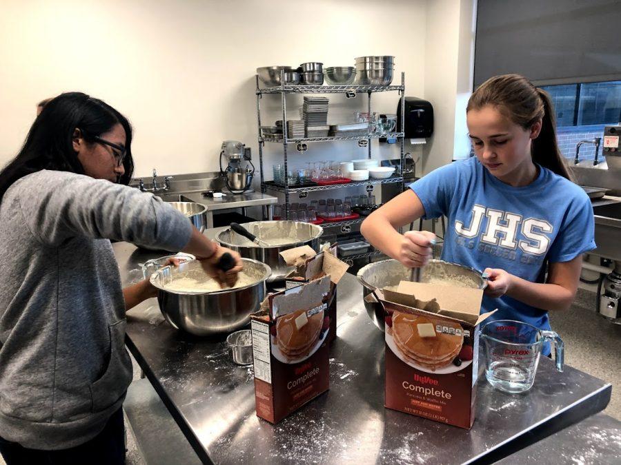 NHS students make pancakes for Santa Pancake Breakfast.