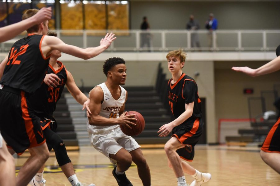 Ty Petty '19 looks to pass the ball while surrounded by 4 Valley players. Petty had one assist off the bench for the Dragons.