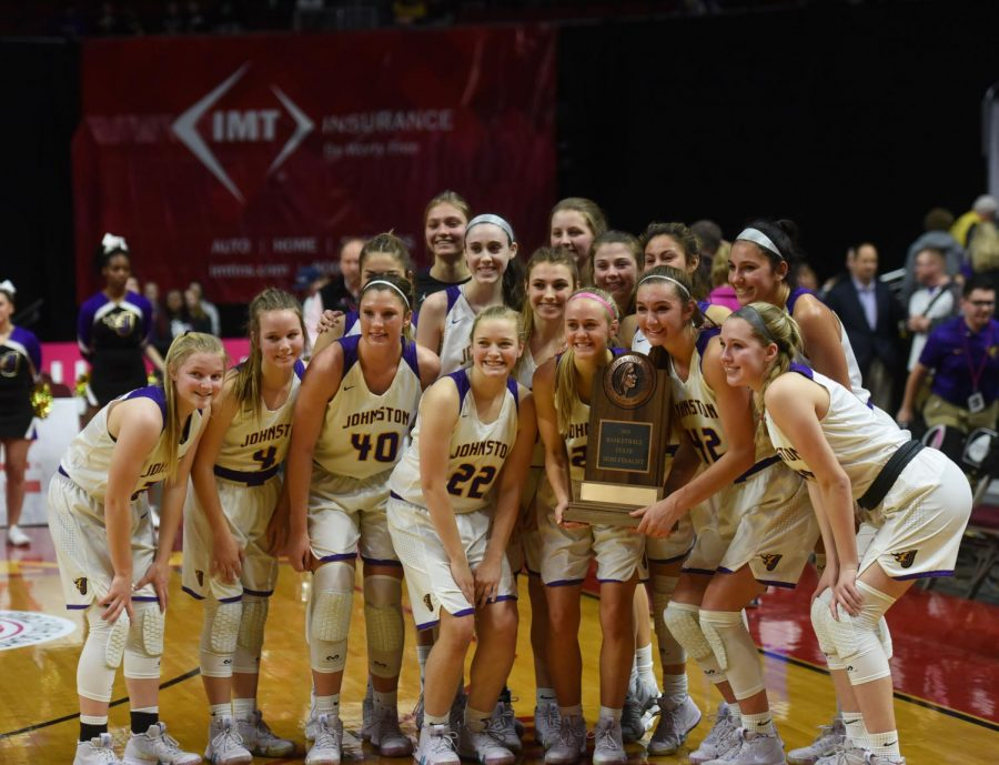 The girls basketball team holds their state semifinalist trophy after their game against West Des Moines Valley on Feb. 28. This was their second straight state semifinal appearance.