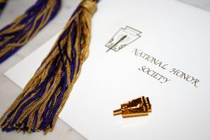 A National Honor Society (NHS) certificate lays next to a NHS pin and the cord NHS members receive at graduation.