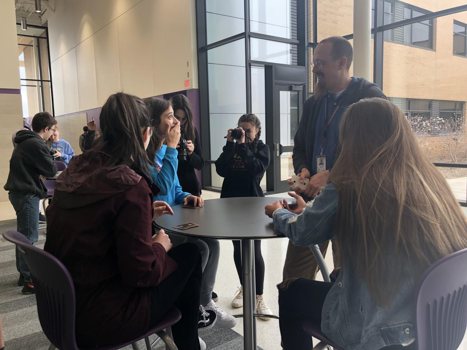 Art teacher Andrew McCormick teaches digital photography students how to play various card games while others take portrait photos of them.