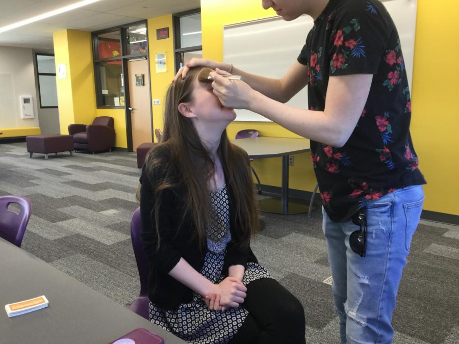 """Sara Gilbreth '21 gets makeup applied during the """"improv FX club"""" in the library."""