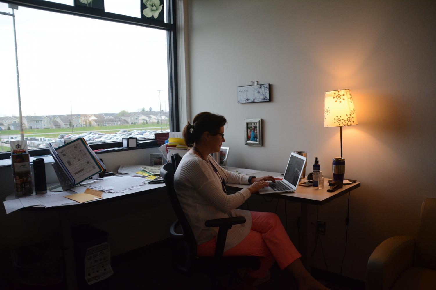 Counselor Erica Woods-Schmitz works at her desk.