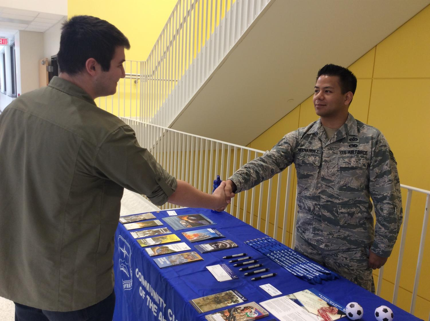 Justin Defenbaugh shaking hands with Air Force recruiter Staff Sergeant Hernandez