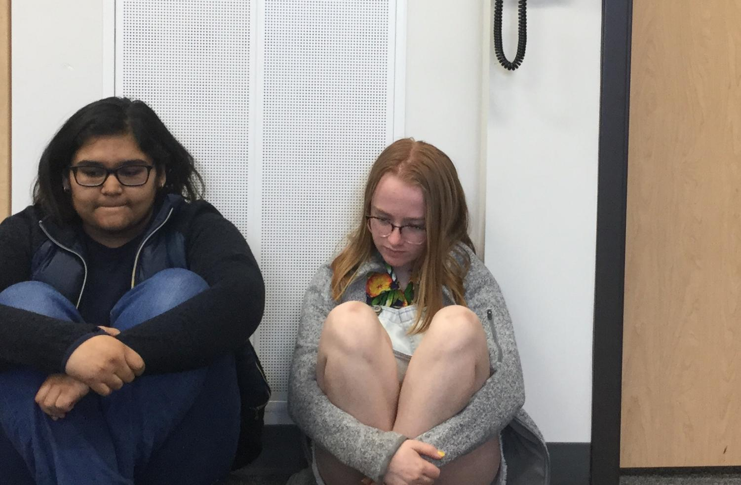 Maryam Mohammed '21 and Morgan Dunn '21 demonstrate the current procedure for intruder drills. The school conducts intruder drills by having students sit against the wall and be quiet, out of view of the hall; this is intended to prevent a shooter from realizing that there are potential victims in a room, but the school more or less glosses over what to do if an intruder gains access to a classroom with people.
