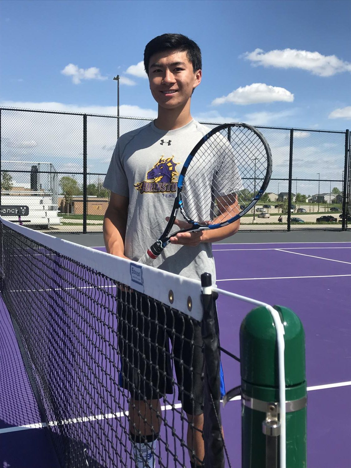 Chris Yao '19 holds his tennis racket on the Johnston tennis courts.