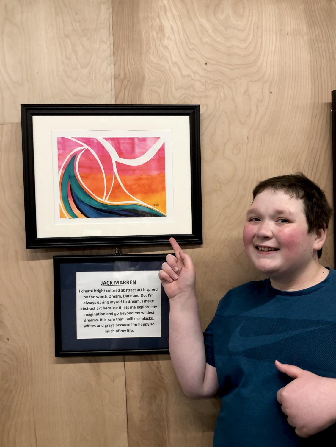 Jack Marren '22 poses for a photo next to his piece that won the t-shirt design contest at the art show at Mainframe Studios on Sep. 6. Underneath the artwork is a statement that he wrote about why he loves this type of art.
