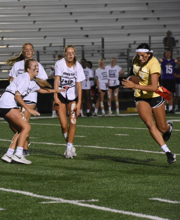 Kendall Nead '20 runs the ball for the seniors while three sophomore defenders look on.