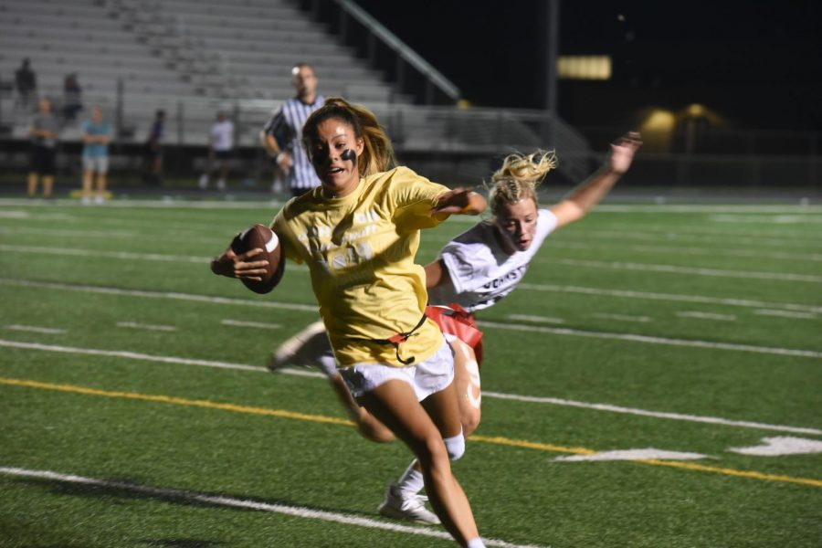 Maya McDermott '20 runs the ball down the field, as a sophomore defender reaches for her flag for the tackle.