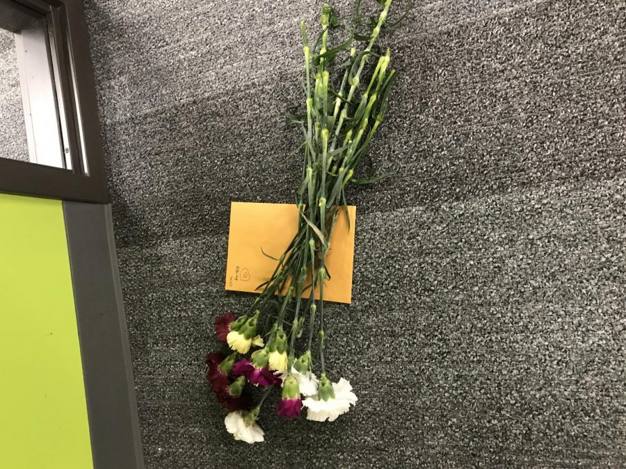 A group of carnations and notes are waiting to be received by a teacher.