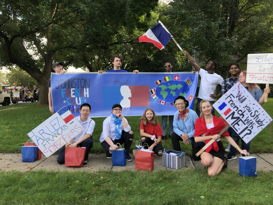 The French Club, sponsored by Tamara Andrews, the French Teacher, posed for a fun picture with their banner and signs encouraging fellow peers to join The French Club.