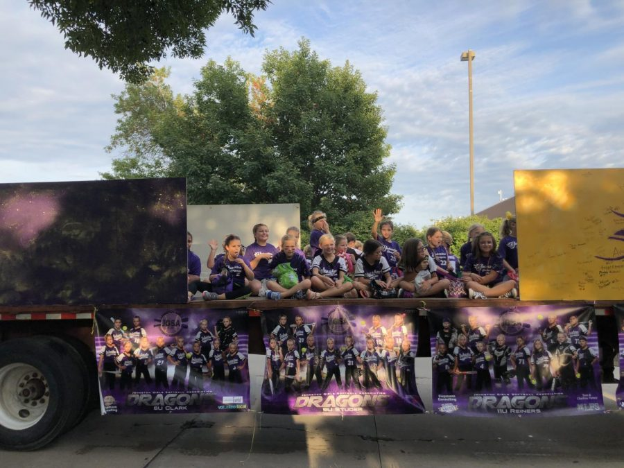 The girls from softball wave at their families and friends watching the parade.