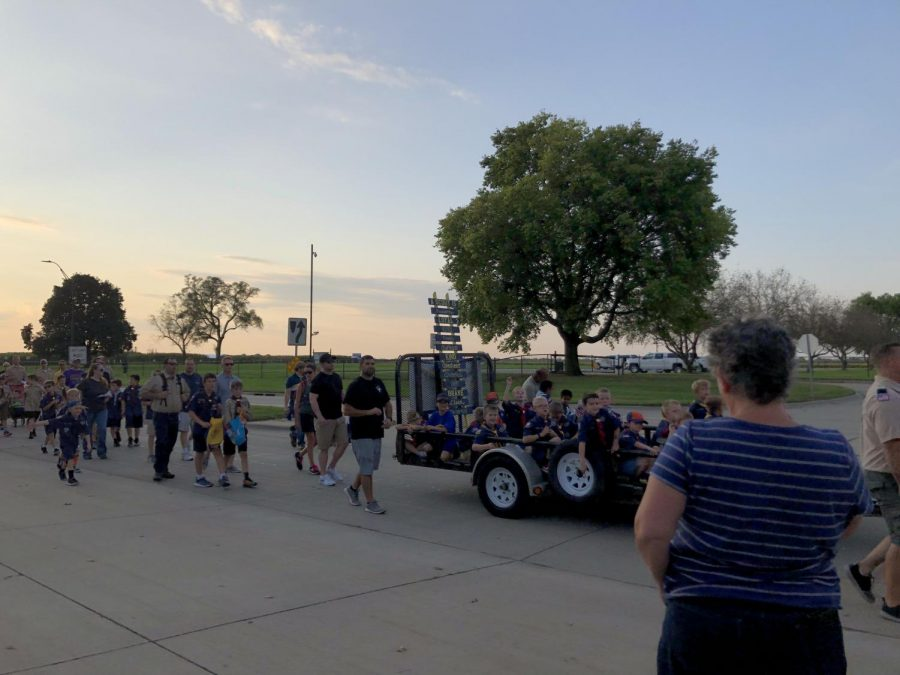 Cub Scouts and Boy Scouts walk and ride on their trailer during the parade.