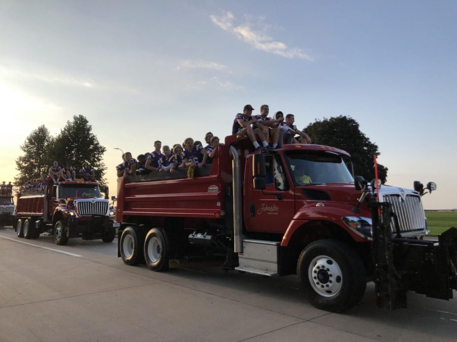 The football team enjoying their ride in a dump truck for the parade.