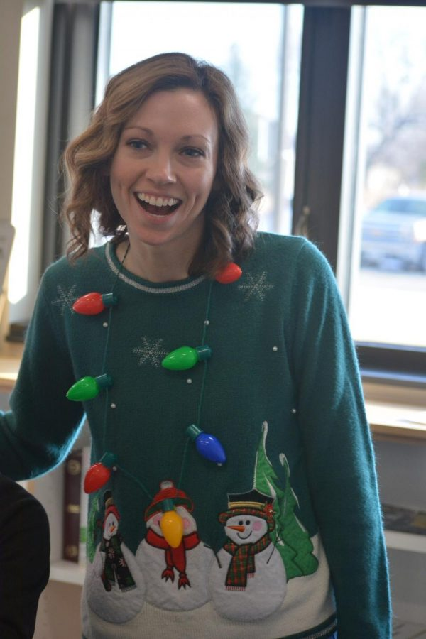 Sarah Love sporting a green ugly Holiday sweater and Holiday lights necklace
