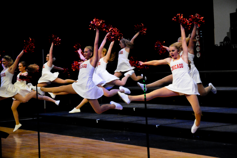 Innovation members leap into the air, pom-poms held high.