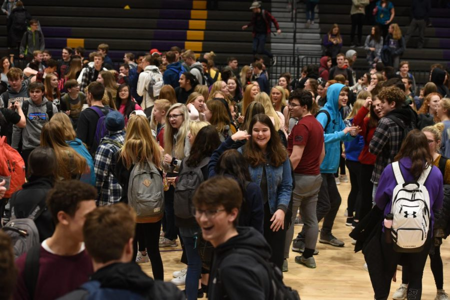 Students dancing and conversing at the end of the concert on the gym floor.