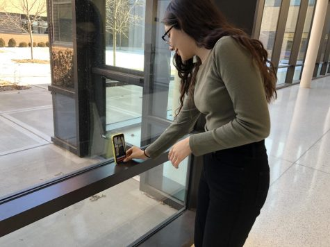 Wendy Avalos '21 setting up her phone on the window in the commons, preparing to