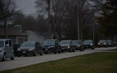 Elementary school teachers lined up in their cars waving and holding signs for their students.