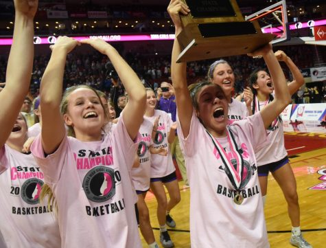Maya McDermott '20 holds the state trophy high before the student section. Last year the girls made it to the state semi-finals where they then lost to West Des Moines Valley