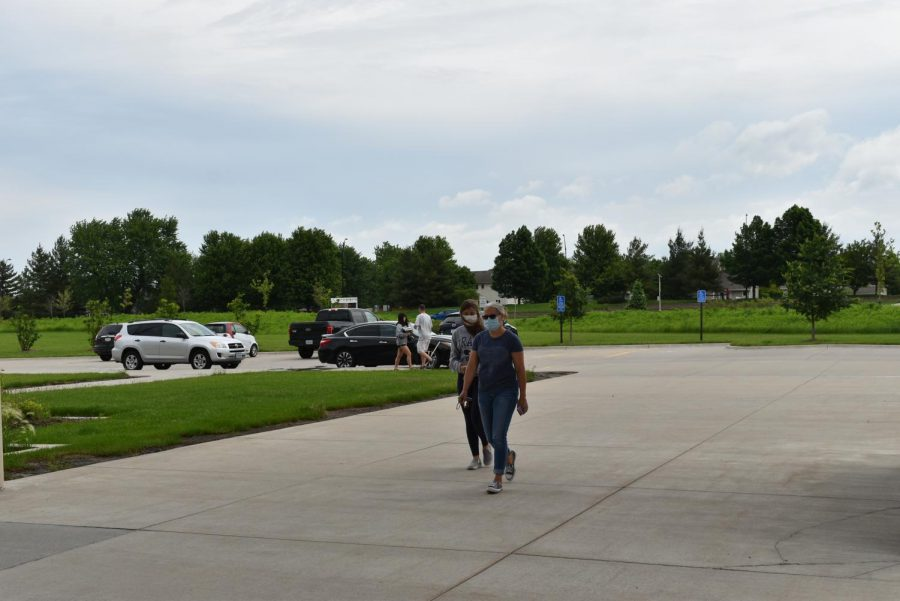 Students and parents walking to the main entrance to pick up items left in lockers.