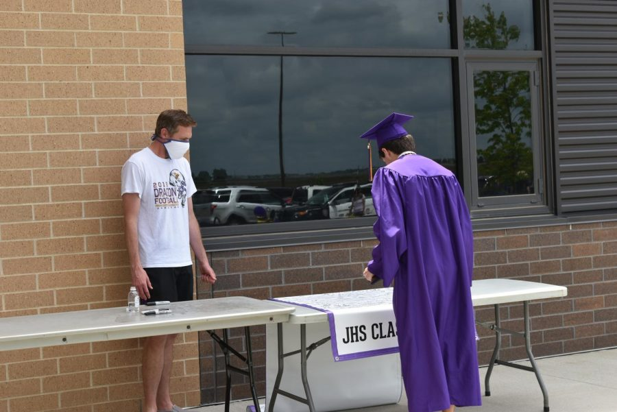 Tyler Miklo sanitizing and supervising the 'JHS Class of 2020' banner where graduates sign their names.