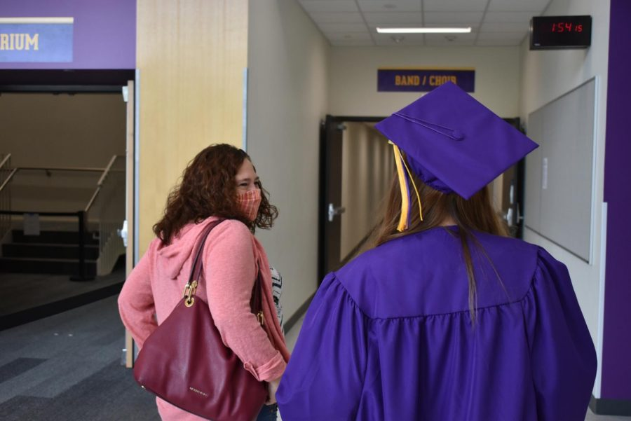 Sophia Rezek '20 and her mother walking towards the auditorium to complete the photo station.