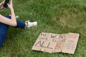 A student sets down their sign crafted from a cereal box as they wait for instruction. Community members staged a march at the middle school June 26 to address inequality and racism in the district.