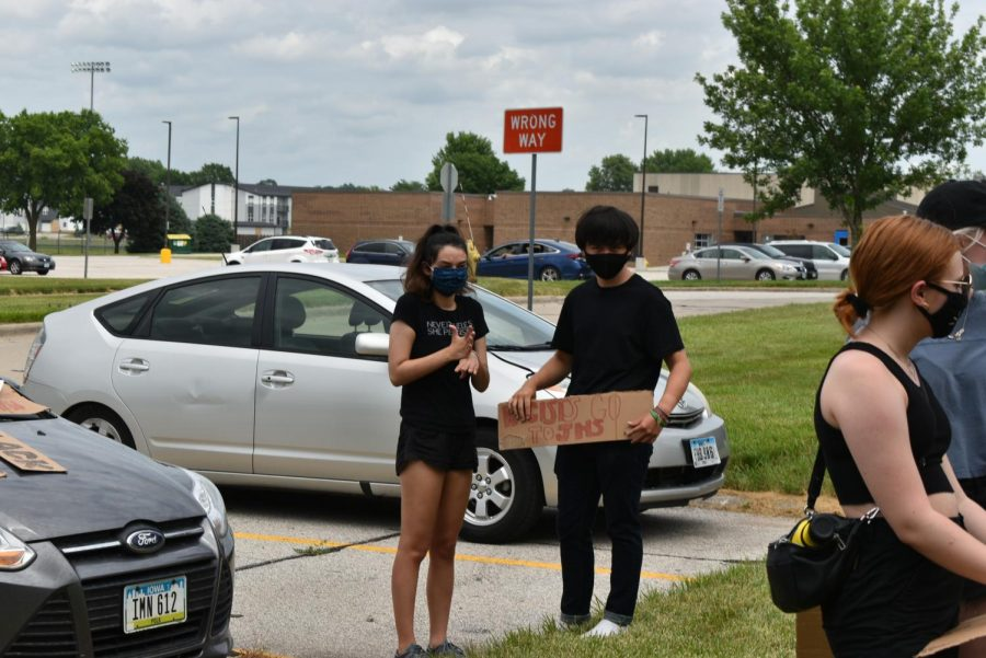 Aidan Weyer '21 holds a sign next to Sophia Flemming '21 as they wait for instruction. Community members staged a march at the middle school June 26 to address inequality and racism in the district.