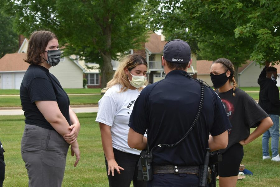 Officer Zach Grandon talks with students about what their plans are for the march, including where they were planning to march to and how they were going to get there. Community members staged a march at the middle school June 26 to address inequality and racism in the district.