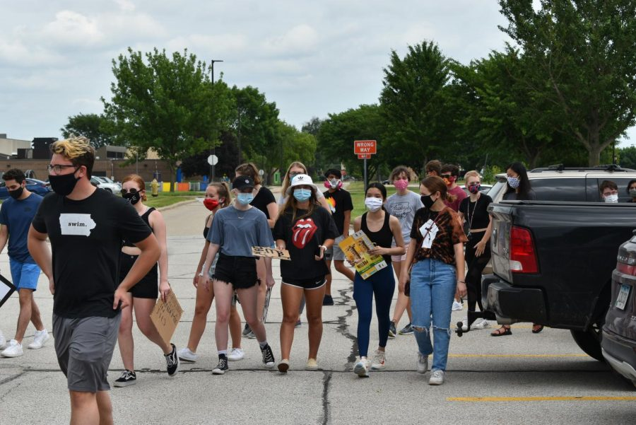 Students and community members walk towards a meeting point to talk with administration about their demands. Community members staged a march at the middle school June 26 to address inequality and racism in the district.