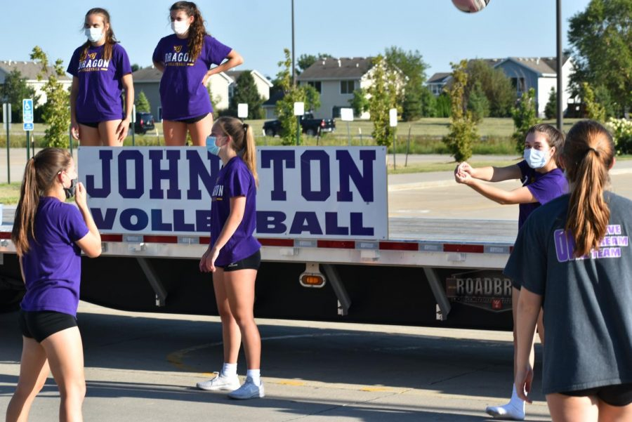 Girl Volleyball platers take trurns passing and serving the volleyball to each other.