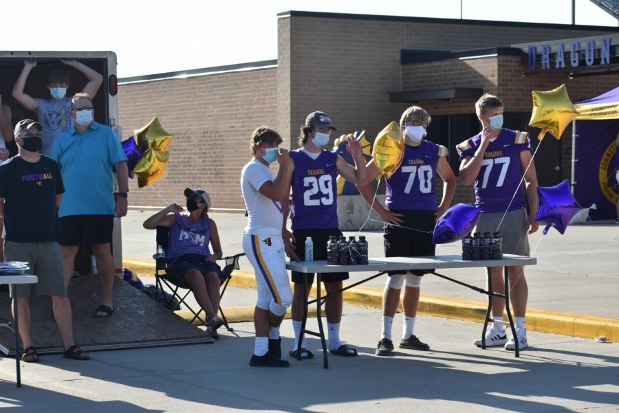 Football players and parents show appreciation for the attendance of the parade.