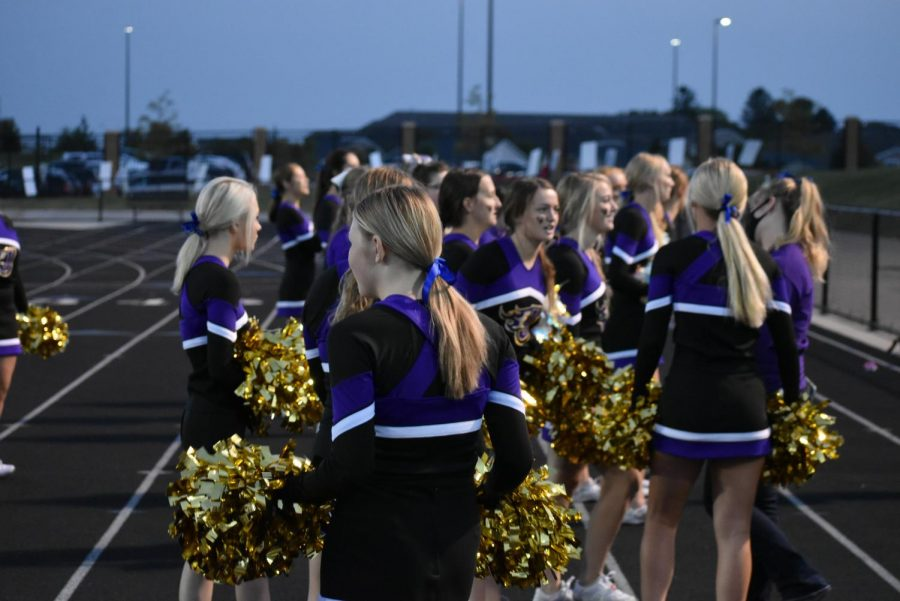 The cheerleaders prepare for a cheer.