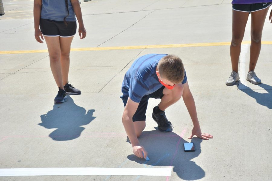 Andy Drafaul '22 mapping out the Technology Student Association (TSA) stadium painting with chalk on Sept. 13 at the high school for homecoming week.
