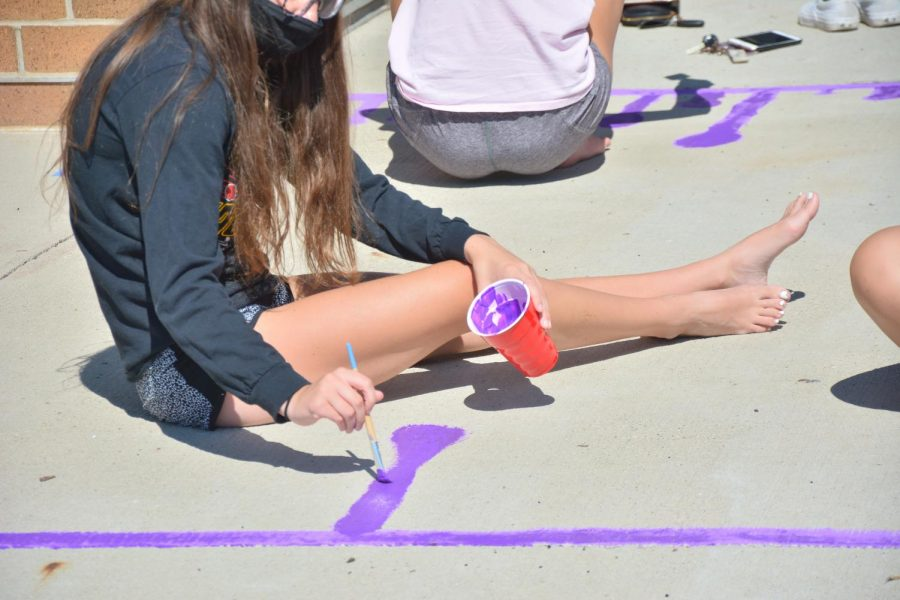 Emily Bertlshofer '21 painting at the stadium on Sept. 13 for the start of homecoming week.