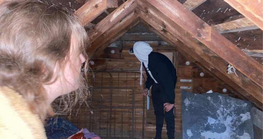 Makenna Pauley '21 on the left watch Nikita Deymich '21 mess with some metal in the attic of the Ax Murder House. The Ax Murder House is located in Villisca, Iowa.