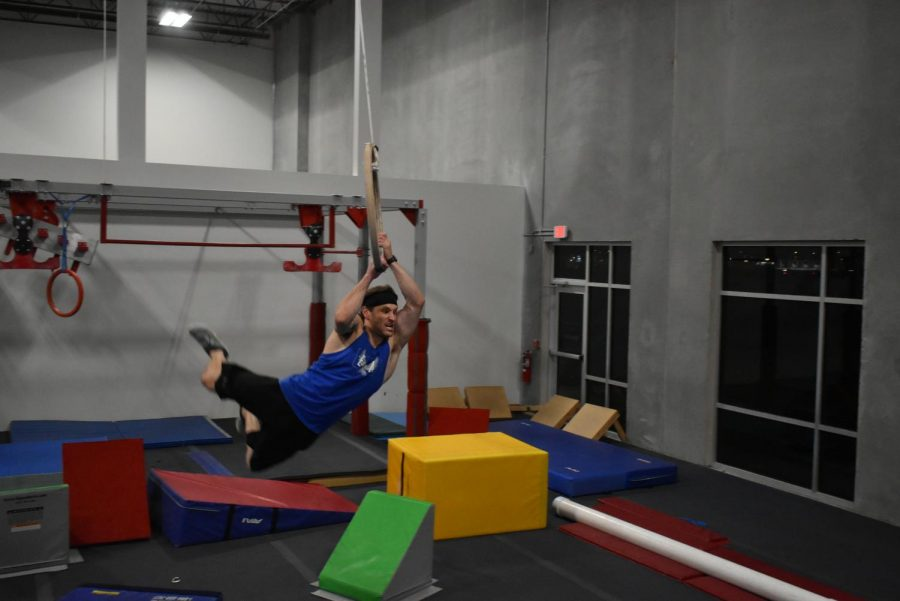 Spencer Johnson flies through the air on a wooden ring attached to the ceiling. A crash pad awaits his landing on the other side.