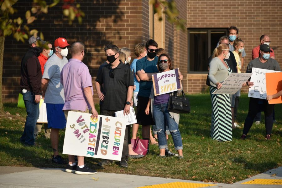 A mother of a student holds a sign  among the crowd.  Supporters of the five-day return to learn plan gathered in front of the district office Oct. 8 to voice their opinions. The board voted 5-2 to scrap the hybrid plan and planned for students to return to school every day Oct. 26.