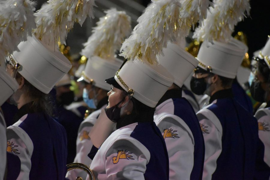 The marching band standing in front of the audience waving goodbye after their final show.